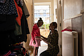 Mother helping daughter with jacket at front doorway