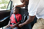 Father fastening seat belt for son in back seat of car