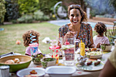 Mother enjoying summer barbecue with family on patio