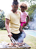 Father holding daughter at barbecue grill