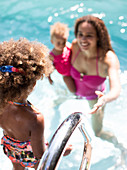 Mother watching daughter get into summer swimming pool