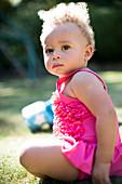 Portrait cute toddler girl in sunny park grass