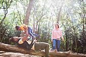 Family playing on fallen log below trees in woods