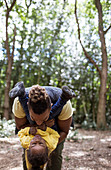 Playful father holding daughter upside down in woods