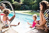 Family relaxing and splashing at summer swimming pool