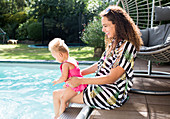Happy mother and toddler daughter at summer poolside