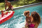 Family playing in sunny summer swimming pool