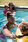 Happy family playing in sunny summer swimming pool