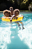 Portrait father and daughters in summer swimming pool