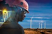 Male engineer in hard hat in field with wind turbines
