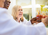 Senior woman enjoying bloody mary cocktail with friends