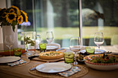 Quiche and salad lunch on dining table with sunflowers