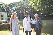 Happy senior women friends walking in summer garden