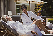 Senior women friends relaxing in spa robes on hotel patio
