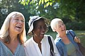 Happy senior women friends laughing in summer garden