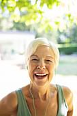 Portrait happy senior woman with headphones in garden