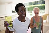 Portrait senior women friends drinking water after workout