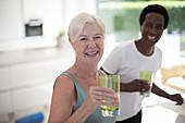 Portrait senior women friends drinking water at home
