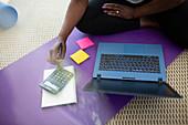 Woman paying bills at laptop on yoga mat at home