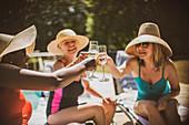 Senior women friends drinking champagne at summer poolside