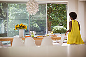 Woman in yellow dress setting dining table for lunch
