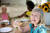 Senior woman drinking white wine with friends at table