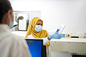 Scientist in hijab and face mask using digital tablet