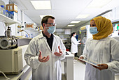 Scientists in face masks talking in laboratory