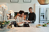 Couple with baby daughter cooking spaghetti in kitchen