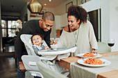 Happy parents feeding baby daughter at dining table