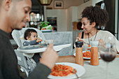 Happy parents and baby daughter eating spaghetti