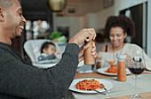 Happy family enjoying spaghetti dinner at dining table