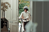 Woman with bicycle returning home at front door