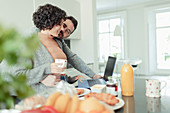 Couple working at laptop in morning kitchen