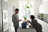 Couple talking and enjoying breakfast at laptop