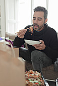 Man eating takeout noodles with chopsticks