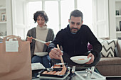 Couple enjoying takeout food with chopsticks