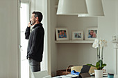 Man talking on smart phone at dining room window