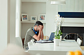 Tired man with head in hands working from home at laptop