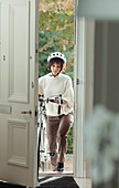 Woman with bicycle returning home through front door