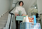 Woman receiving grocery delivery crates in foyer