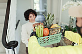 Grateful woman receiving grocery delivery at home