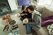 Couple enjoying takeout food with chopsticks on sofa