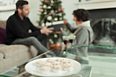 Wife opening Christmas gift behind tray of mince pies