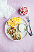 Potato and spinach burgers served with polenta, horseradish sauce and tomato salad