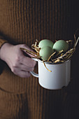 Woman holding a cup with green hen's eggs