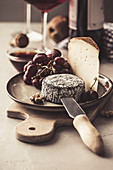 Cheese plate with fruits, nuts and red wine