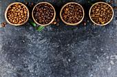 Vier verschiedene Sorten von Kaffeebohnen in Holzschalen