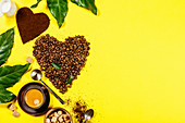 Coffee beans in shape of heart and cup of coffee on yellow background
