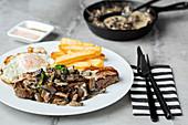 Steak mit Pilzen, Spiegelei und Pommes